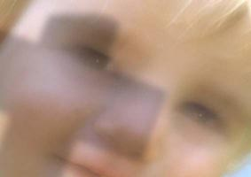 EN SÅN GUD SKULLE JAG KUNNA TRO PÅ: Närbild av ett barnansikte, som är så ljust att det egentligen bara syns på avstånd. Över ansiktet faller skuggan av ett kors. Foto:Per Johansson
