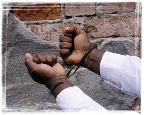NÖDEN HAR INGEN LAG: Händer i handbojor. Om man tittar noga, ser man att bojorna är ett paragraftecken Foto: Per Johansson