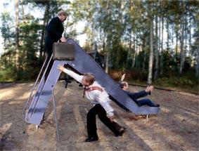 EN GÅNG TILL: Tre män i kostym, slips och dokumentportfölj åker rutschkana.  Foto: Per Johansson