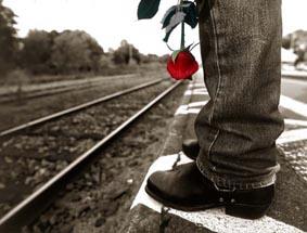 KVAR PÅ PERRONGEN: Ett jeansklätt ben i en sko, som står på perrongen, nära rälsen. Allt är svart-vitt, utom den röda rosen.  Foto: Per Johansson