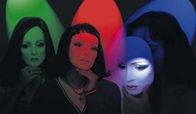"""PLASTIC PARADISE: Tre tjejer i """"club-belysning"""". Dom håller en varsin identisk mask för ansiktet. Maskerna är perfekta, men kyliga. Den ena masken är inte fullt på. Foto: Per Johansson"""